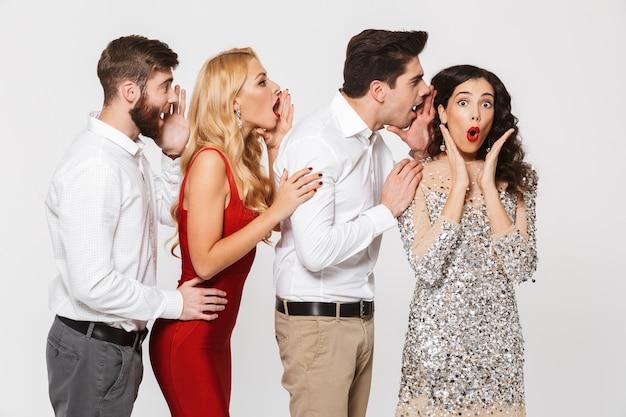 Группа из четырех веселых людей, умно одетых, рассказывающих секреты друг другу, изолированные на белом