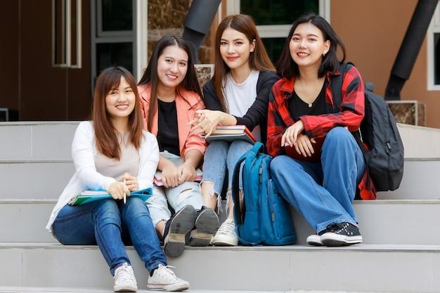 本を持って、座って、学校の外で時間を共有している4人の大学生の女の子のグループ