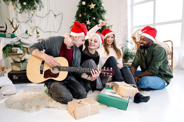 家でクリスマスを祝ってギターを弾き、キャロルを歌う4人の友人のグループ