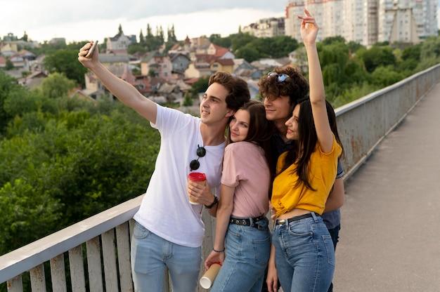 屋外で一緒に時間を過ごし、自分撮りをしている4人の友人のグループ