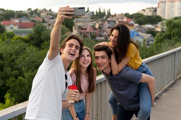 Группа из четырех друзей, проводящих время вместе на открытом воздухе и делающих селфи