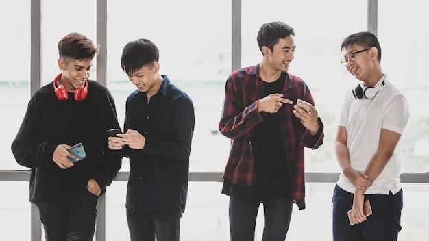 Группа из четырех красивых молодых мужчин-подростков с милой улыбкой стоя и разговаривает друг с другом. младшие мальчики играют в смартфон и разговаривают. понятие отношения друзей колледжа