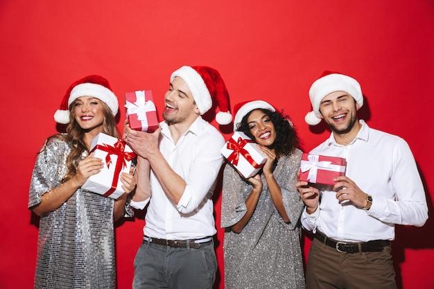 Группа из четырех счастливых, элегантно одетых друзей, стоящих изолированно над красным пространством, празднует