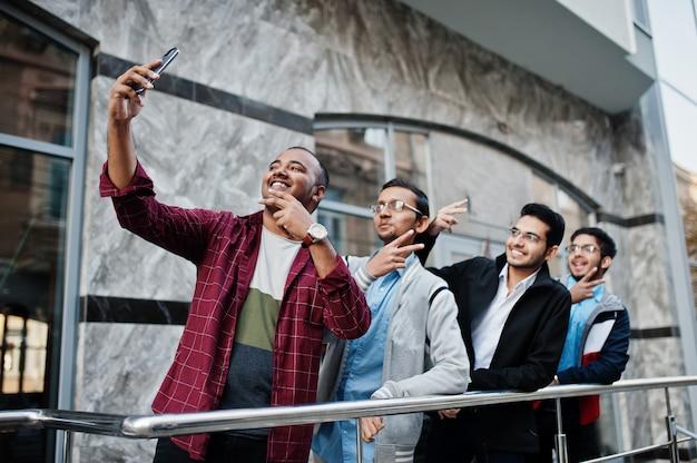 Группа из четырех индийских подростков студентов мужского пола. одноклассники проводят время и делают селфи по телефону вместе.