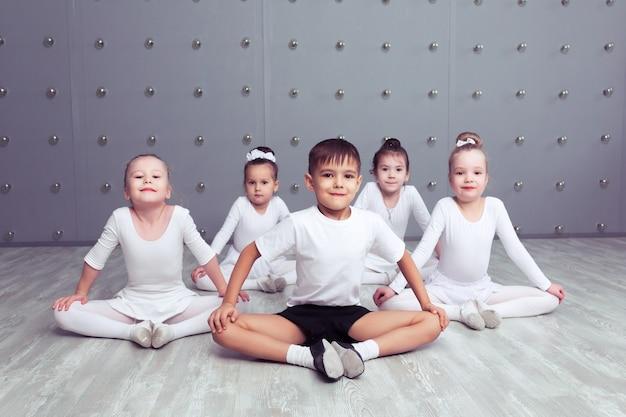 4人の小さなバレリーナと子供バレルンが一緒にポーズをとって練習しているグループ