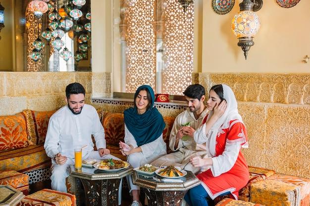 Группа из четырех друзей мусульман в ресторане