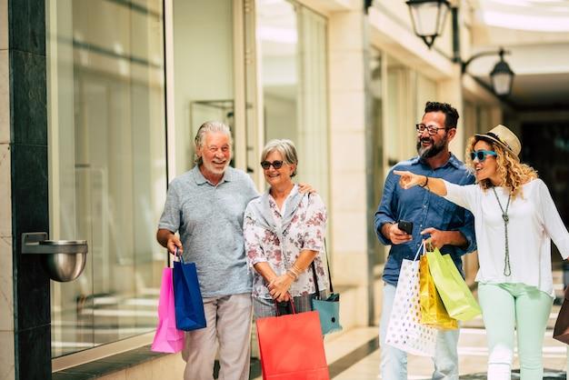 크리스마스 선물이나 선물이 든 쇼핑백을 들고 함께 쇼핑을 하는 4명의 그룹 - 쇼핑몰이나 일부 상점에서 옷 등을 구입