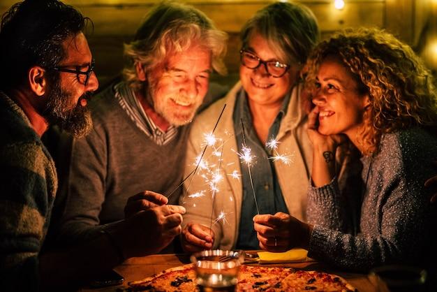 Группа из четырех человек, таких как пожилые люди и взрослые, встречает новый год нового года вместе с бенгальскими огнями и пиццей.