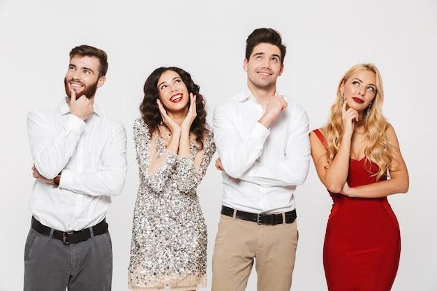 Группа из четырех улыбающихся людей, умно одетых, глядя на копию пространства, изолированного на белом