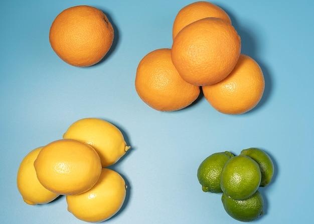 青い背景の上の新鮮な柑橘系の果物のグループ