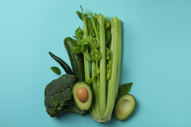 青い背景の上の新鮮な緑の野菜のグループ