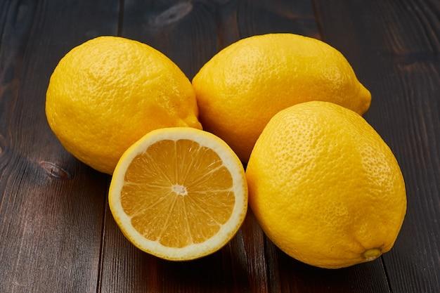 暗い木製のテーブルに新鮮なジューシーレモンのグループ