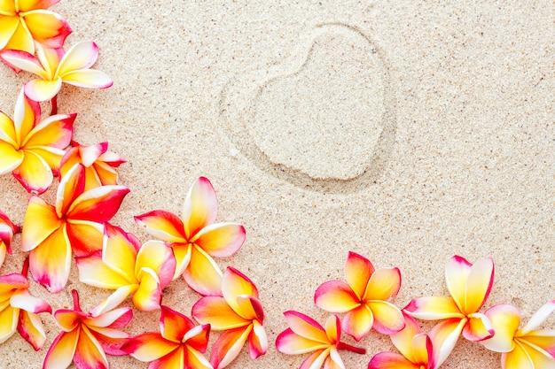 Группа свежих розовых и желтых цветов франжипани или плюмерия на песке с фоном печати сердца