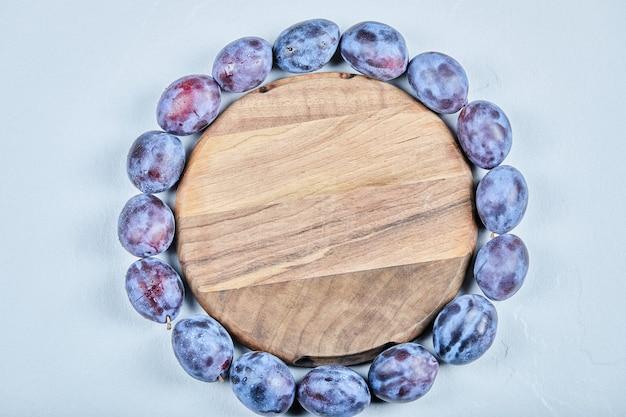Группа свежих слив вокруг деревянной тарелки. фото высокого качества