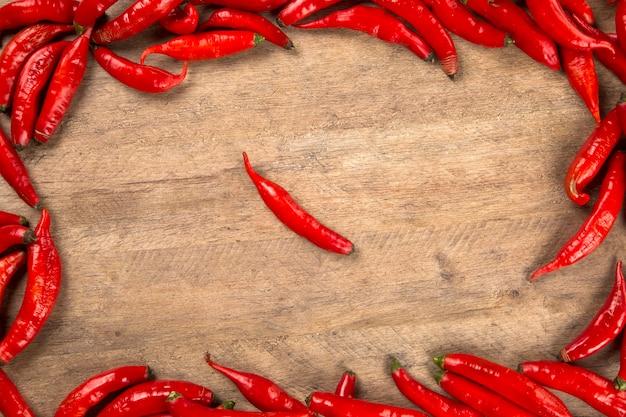 木製の背景に新鮮な赤唐辛子のグループ。新鮮な唐辛子。