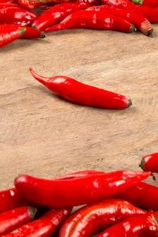 Группа свежих красных острых перцев на деревянном столе. свежий перец.