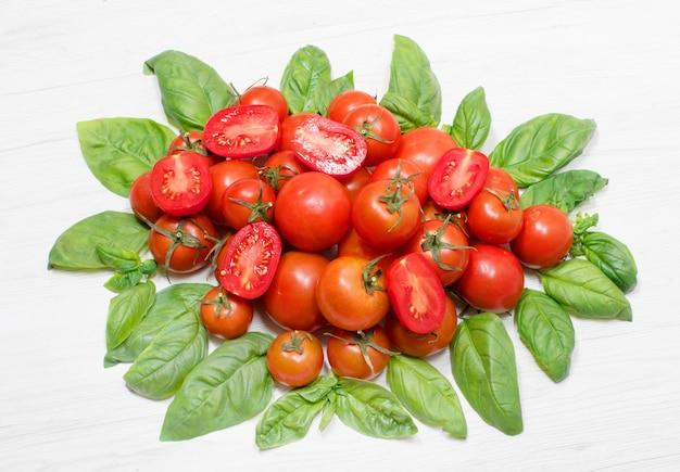 신선한 빨간 토마토와 신선한 바질의 녹색 잎의 그룹 프리미엄 사진