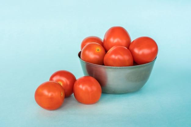 Группа свежих помидоров в ведре на синем фоне. фото крупным планом