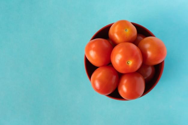 Группа свежих помидоров в ведре на синем фоне. вид сверху крупным планом фото