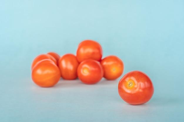 Группа свежих помидоров на синем фоне. фото крупным планом