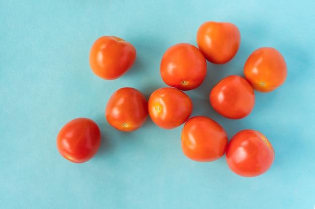 Группа свежих помидоров на синем фоне. вид сверху крупным планом фото