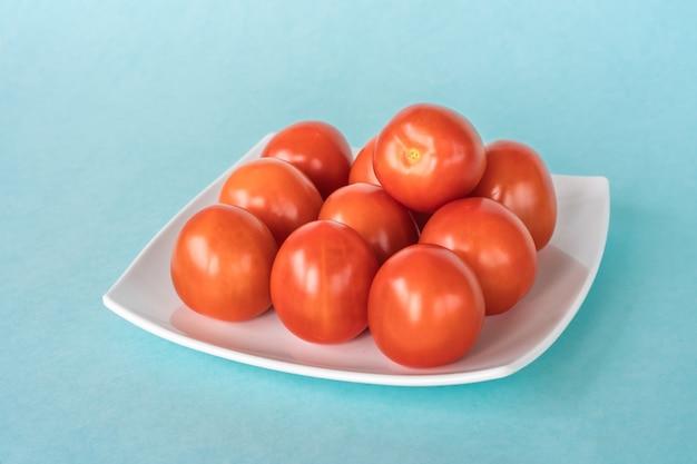 Группа свежих помидоров на белой тарелке на синем фоне. фото крупным планом
