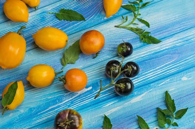Группа свежих помидоров на синем деревянном фоне