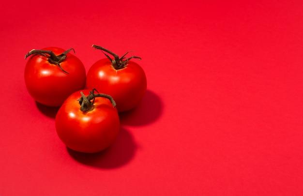 赤いテーブルに提示された新鮮なトマトのグループ