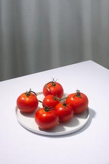 白いテーブルに提示された新鮮なトマトのグループ