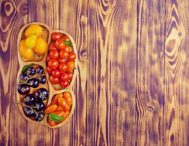 Группа свежих помидоров. помидоры разных цветов и видов в деревянной миске