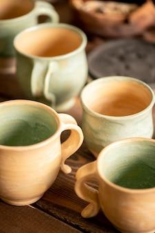 Группа свежеприготовленных глиняных чашек в ожидании дальнейшей обработки на рабочем месте гончара в мастерской