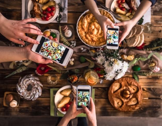 Группа друзей сфотографировать с мобильного телефона, прежде чем обедать. вид сверху.