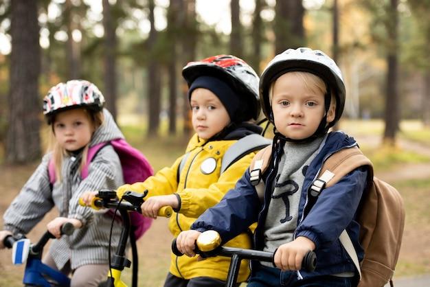 Группа дружелюбных маленьких детей в повседневной одежде и защитных шлемах, сидящих на беговелах перед камерой во время отдыха в общественном парке