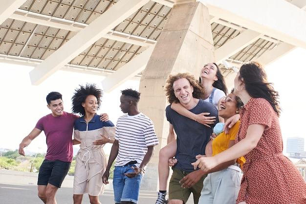 Группа дружелюбных многонациональных друзей веселится, молодые студенты обнимаются за пределами университета