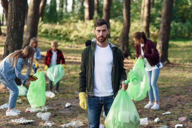 Группа друзей-активистов собирает мусор в парке