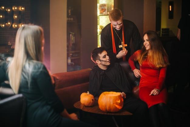 Группа друзей празднует хэллоуин в кафе. парень одет как ужасный священник и монстр. красивая сексуальная девушка в красном платье, сидя на софе. съемка в комнате с черно-красными стенами