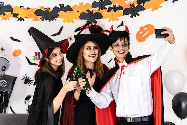 Группа друзей азиатских молодых взрослых людей празднует вечеринку в честь хэллоуина. они носят костюмы на хэллоуин и делают селфи. празднование хэллоуина и концепция международного праздника.