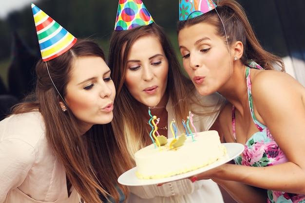 バースデーケーキにろうそくを吹く友人のグループ