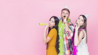 Group of friends blowing party horn on pink background