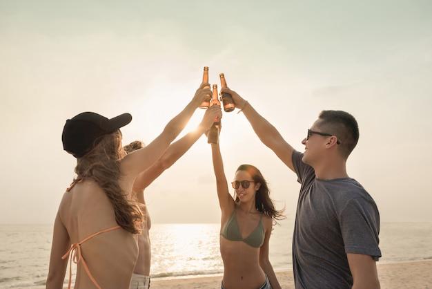 Группа друзей, празднование и пить на пляже в сумерках