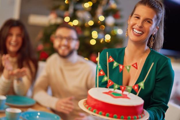 X-massケーキを楽しんで家でクリスマスを祝う友人のグループ Premium写真