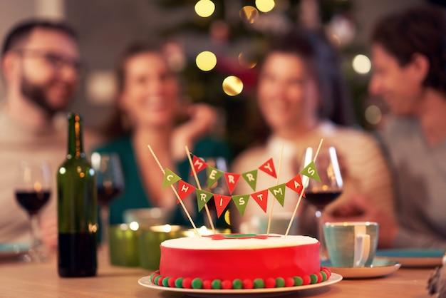 X-massケーキを楽しんで家でクリスマスを祝う友人のグループ