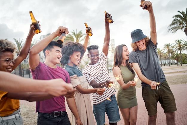 Группа друзей празднует с блестками и пивом, люди разных рас, хорошо проводят время в ...