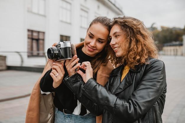 プロのカメラをチェックしている友人のグループ