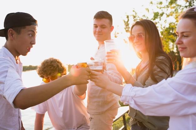 Группа друзей, звенящих пивными бокалами во время пикника на пляже в лучах солнца. образ жизни, дружба, развлечения, выходные и отдых концепции. выглядит бодро, весело, празднично, празднично.