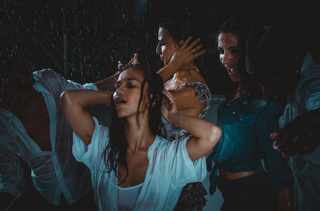 Группа друзей, танцующих под дождем