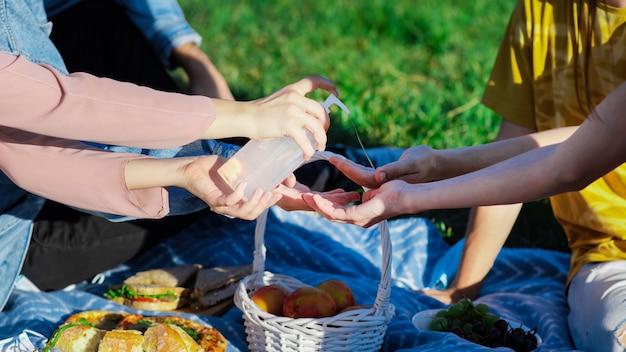 ピクニックで手を消毒する友人のグループ