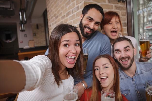 Группа друзей, пьющих пиво в пабе вместе