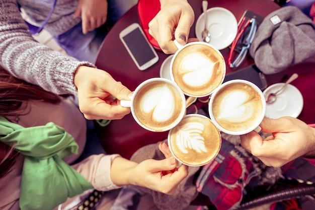 コーヒーバーレストランでカプチーノを飲む友人のグループ