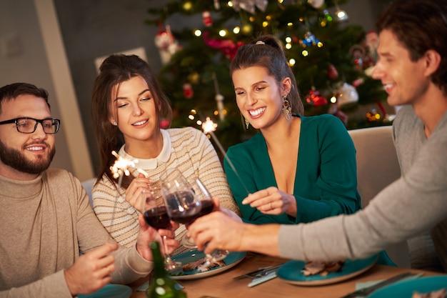家でワインを飲み、クリスマスを祝う友人のグループ